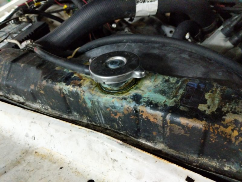 Radiator filler neck with lots of radiator fluid (glycol) crusted around it.
