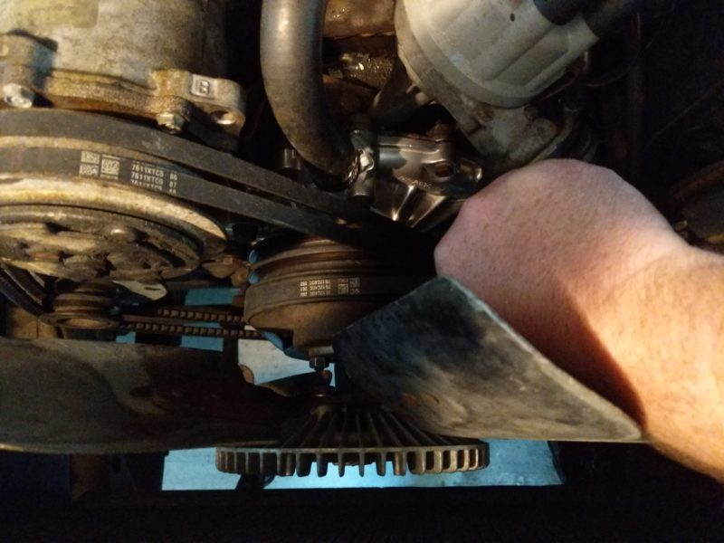 Using the belts to get friction while tightening the fan clutch stud nuts.